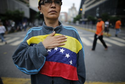 A woman holds a Venezuelan flag on her chest as she joins a roadblock in Caracas, Venezuela, Tuesday, May 2, 2017. Residents blocked streets with trash bags, broken concrete and twisted metal Tuesday to protest the president's bid to rewrite the constitution amid a deepening political crisis. (AP Photo/Ariana Cubillos)